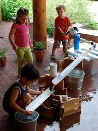 summer childcare program kids playing with rain gutter and water